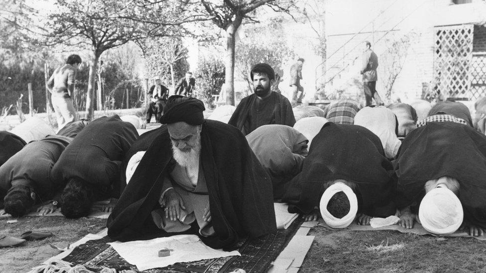 الخميني يصلي في حديقة منزله بمنفاه في فرنسا