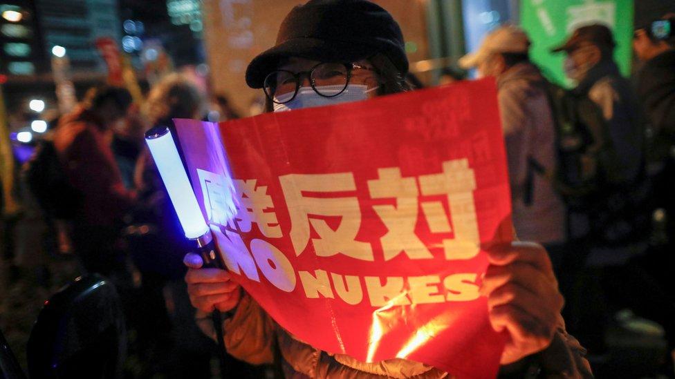 日本反核示威者在東京電力公司東京總部外舉起「反對原發」標語牌(11/3/2021)