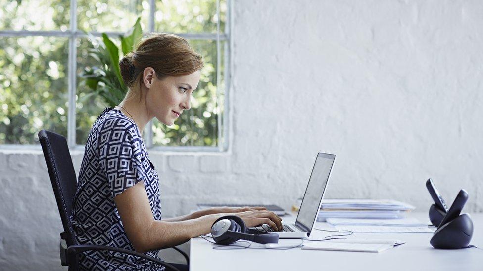 Mujer sentada frente a una laptop