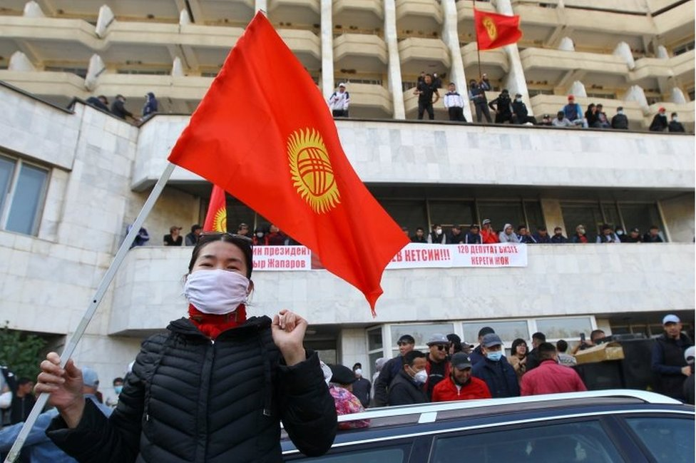 "A woman holds the national flag as supporters of Kyrgyzstan""s Prime Minister Sadyr Japarov attend a rally in Bishkek, Kyrgyzstan October 15, 2020."
