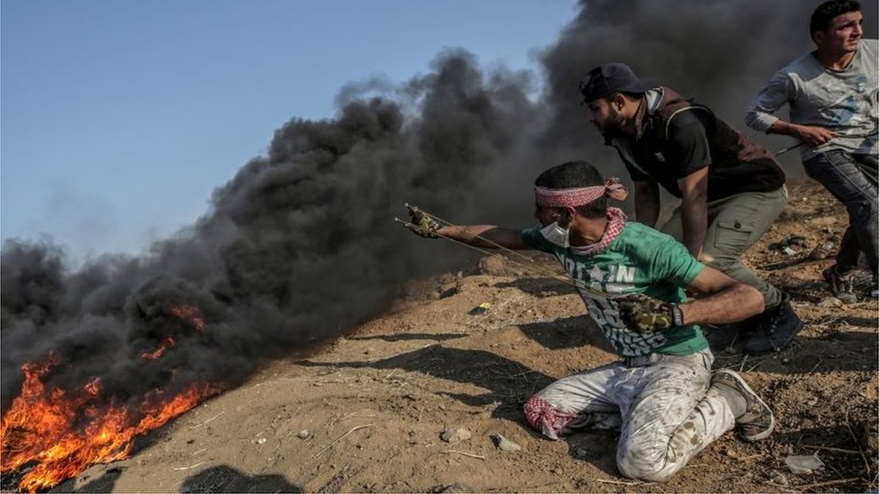 Palestinian prepares to fire a slingshot at a Gaza border protest (15/05/18)