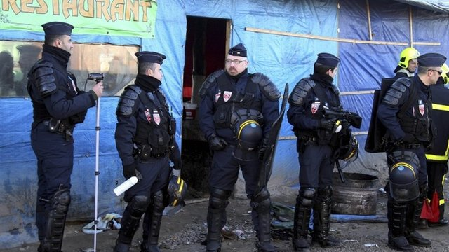French riot police officers stand at the entrance of the Calais migrant camp, northern France Thursday, Jan.21, 2016.