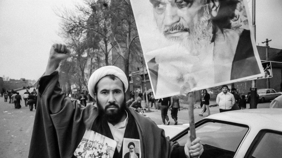 A Shia cleric holds up a banner showing Ayatollah Ruhollah Khomeini during Iran's 1979 Islamic Revolution