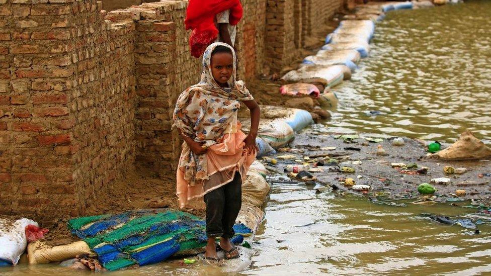 فتاة سودانية تسير وسط مياه الفيضانات.