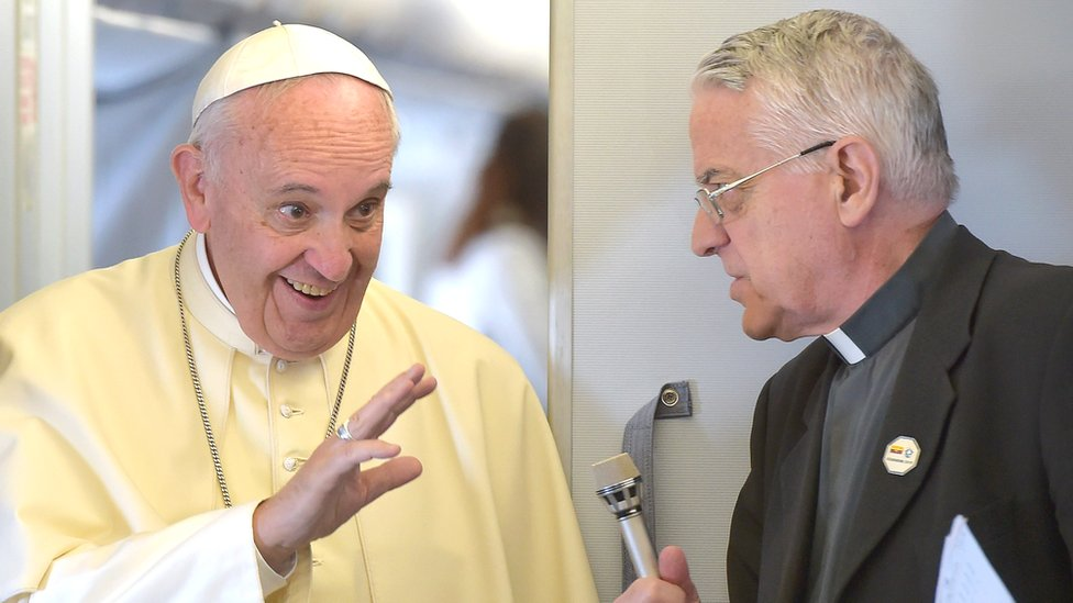 Pope Francis (L) talks with Father Federico Lombardi as he arrives to welcome the journalists on board the flight to Ecuador's capital Quito on 5 July, 2015.