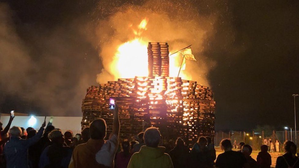 Crowds of people watch as the bonfire at Avoniel Leisure Centre burns