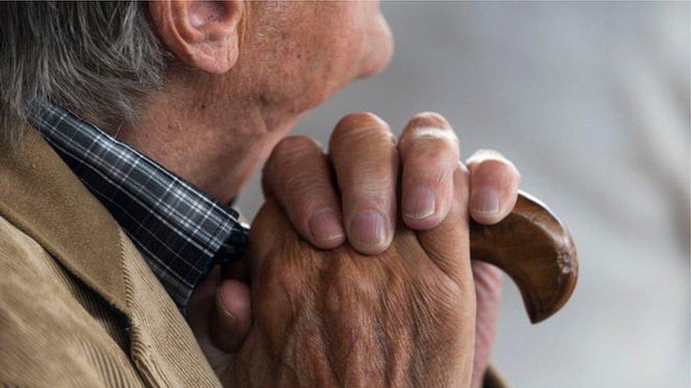 Čovek sede kose drži štap u ruci