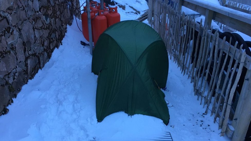 Couple's green tent behind the Charles Inglis Clark (CIC) memorial hut on the north side of the mountain