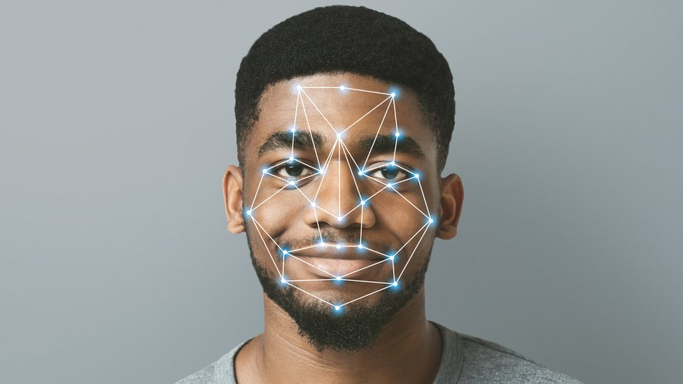 A stock image shows a black man smiling at the camera, while a network of lights and dots is superimposed over his face to illustrate the concept of facial recognition