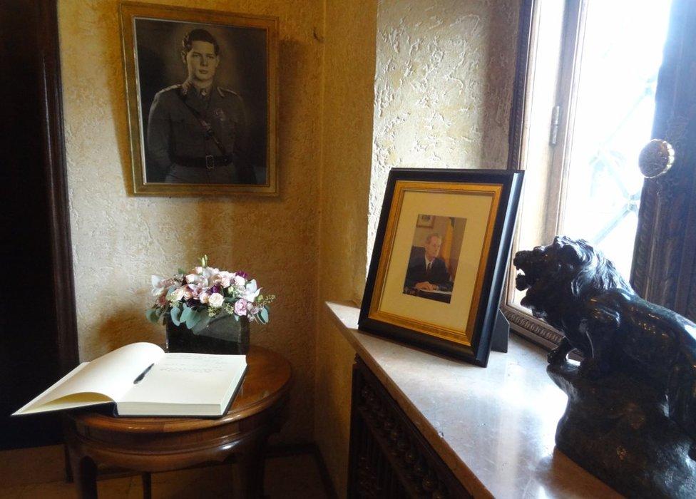 A book of condolences lies beneath a portrait of the king at Bucharest's Elisabeta Palace