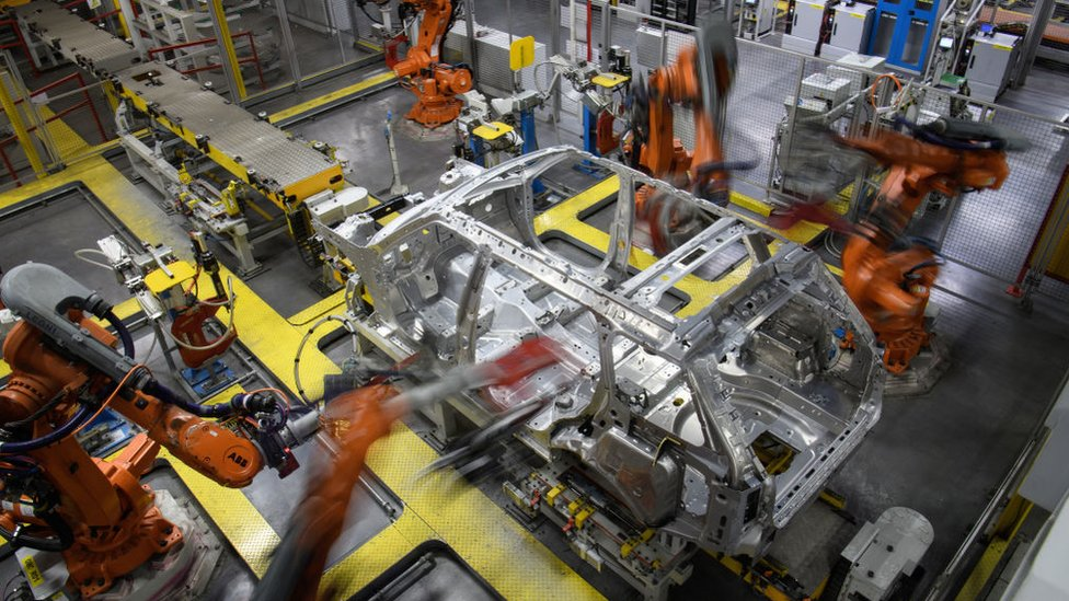 Robotic systems work on the chassis of a car during an automated stage of production at the Jaguar Land Rover factory