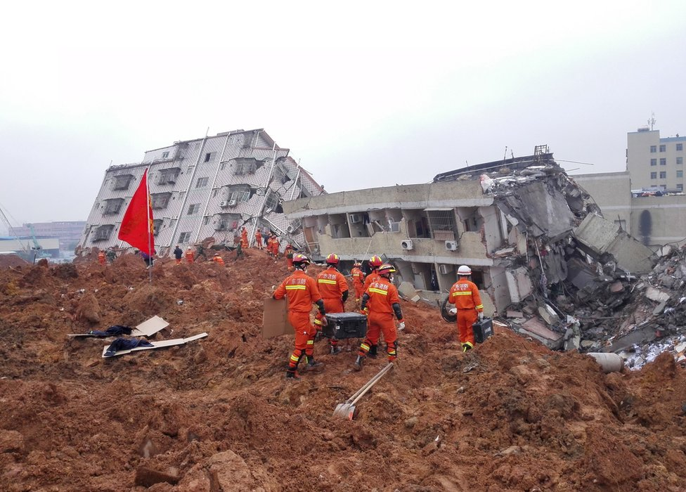 Firefighters search for survivors among the rubble of collapsed buildings after a landslide hit an industrial park in Shenzhen, Guangdong province, China, 21 December 2015.