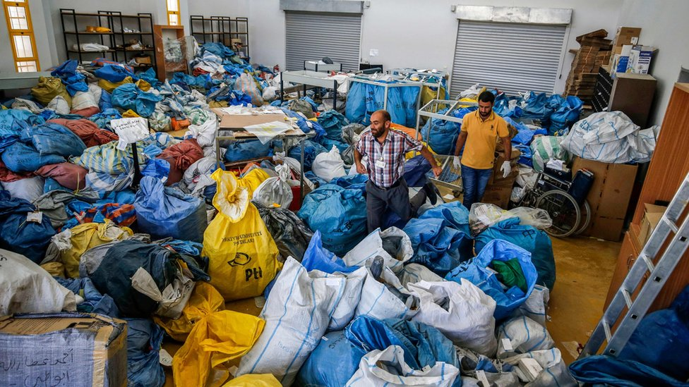 Palestinian postal workers sift through sacks of previously undelivered mail in the West Bank city of Jericho, 14 August 2018
