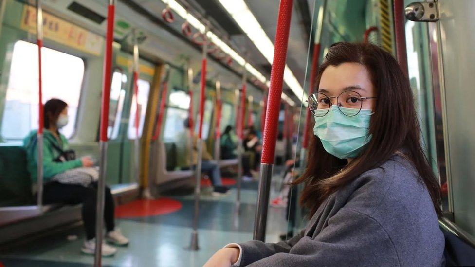 Jovem mulher de máscara sentada no metro olha para a camera