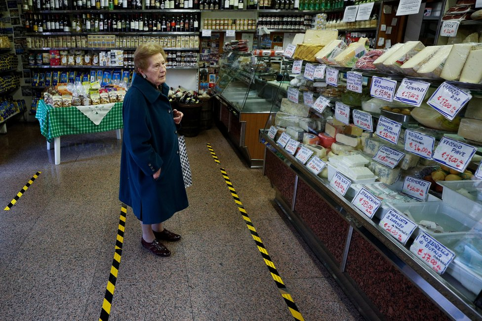A lady waits to be served in a food shop