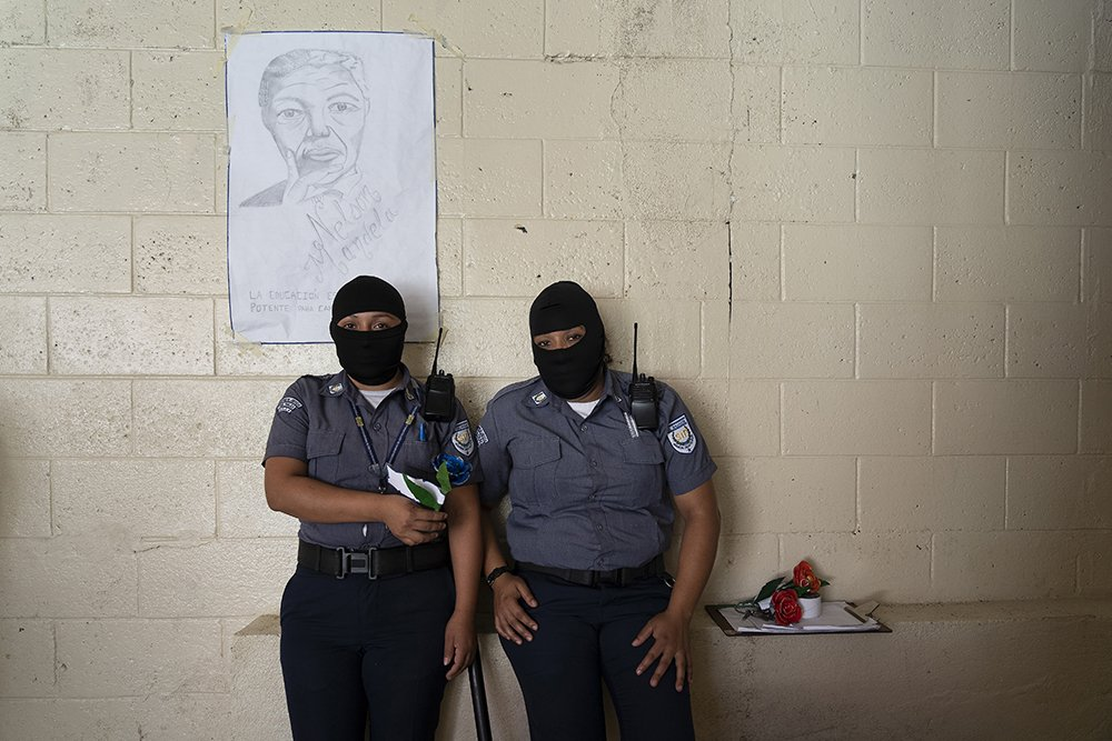 Women prison guards, wearing balaclavas to protect their identities, stand in front of a portrait of Nelson Mandela at the Penal Center of Quezaltepeque, El Salvador. November 9, 2018.