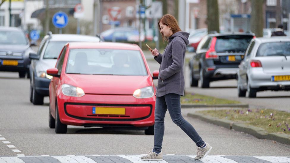 Una mujer mira su celular mientras cruza la calle y no ve los autos.