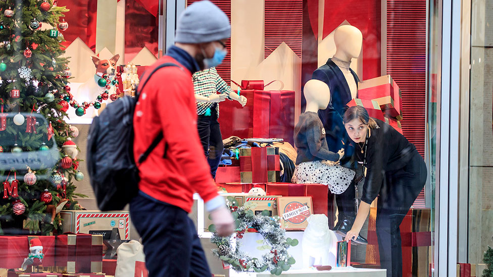 Man passing a Christmas shop window display in Manchester