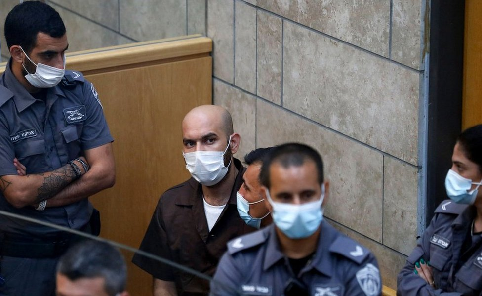 Palestinian Ayham Kamamji, 35, is surrounded by Israeli police officers as he appears at the magistrates' court in the northern Israeli city of Nazareth, on September 19, 2021