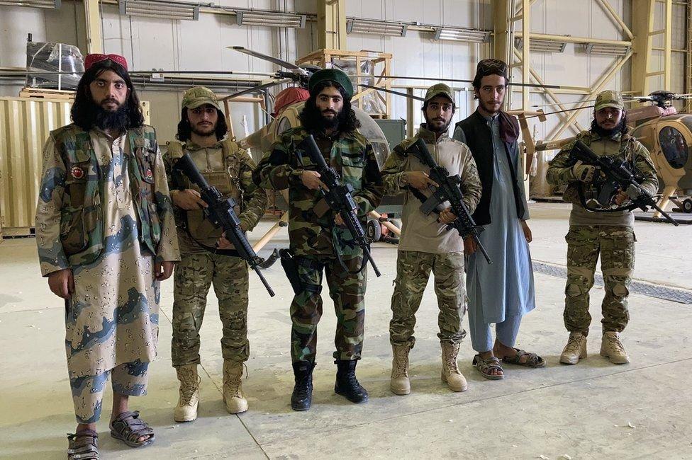 مقاتلو طالبان يقفون أمام مروحيات الجيش السابق في مطار بلخ