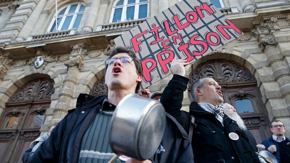 "Demonstrators protest with pots and a placard that reads ""Fillon in prison"" - 17 February 2017"