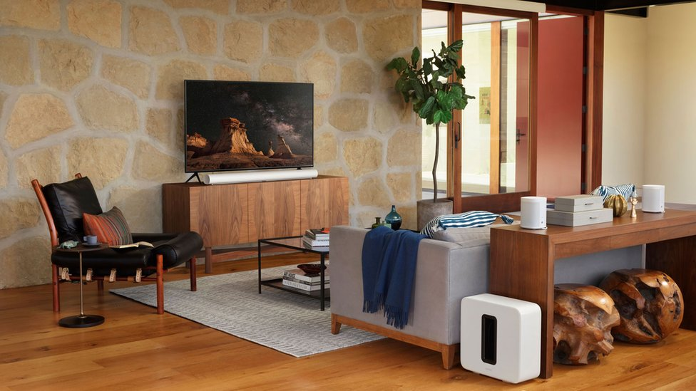 The Sonos soundbar is seen in a very expensively furnished stage home, complete with matching subwoofer and rear speakers