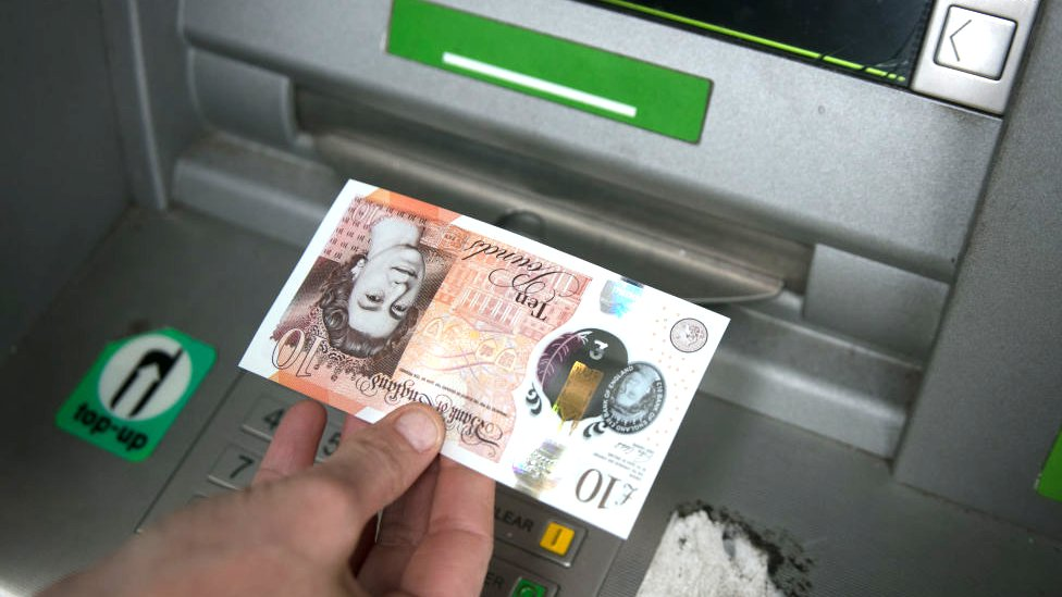 Ten pound note being withdrawn from a cash machine