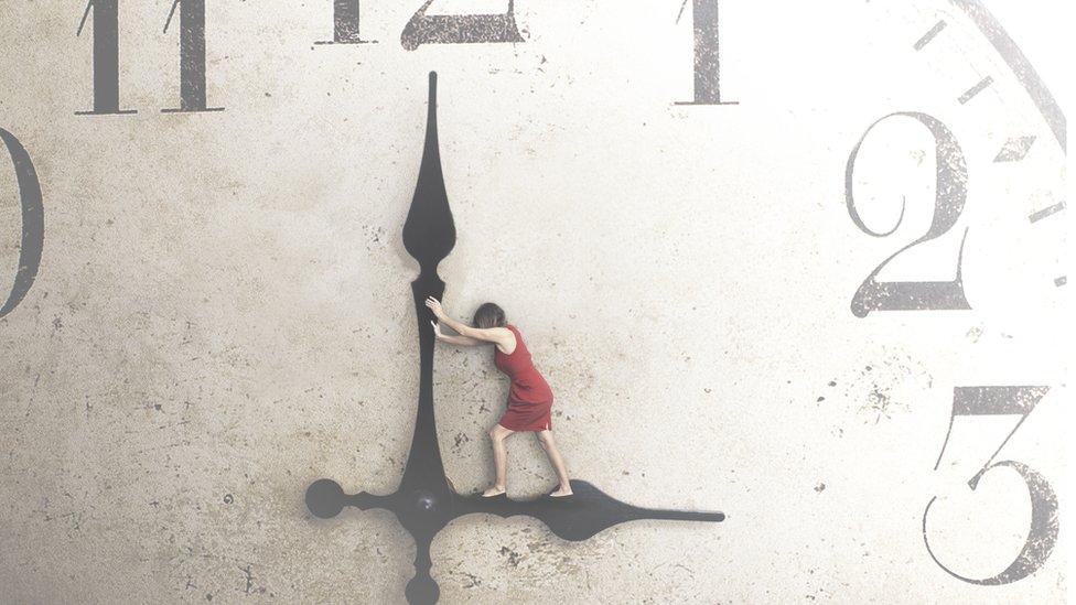 Una mujer intenta mover las agujas del reloj.