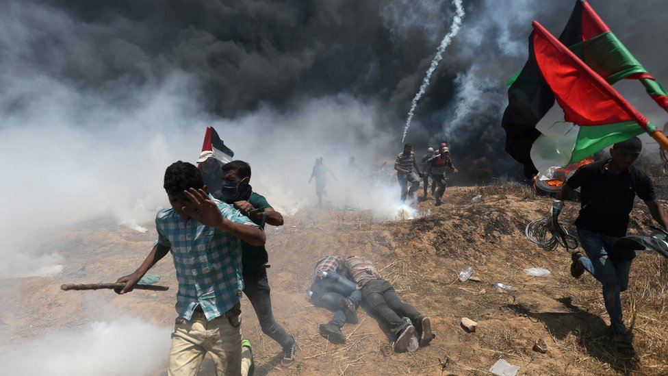 Palestinians run for cover during a protest near the Gaza-Israel border fence (14 May 2018)