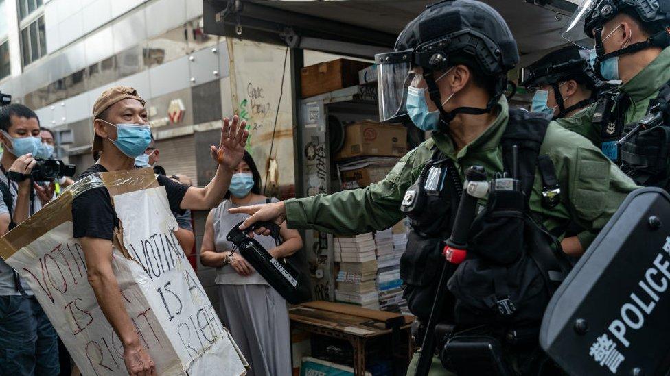 Seorang pria mengenakan Voting Is A Right costome berselisih dengan polisi anti huru hara selama protes anti-pemerintah pada 6 September 2020 di Hong Kong
