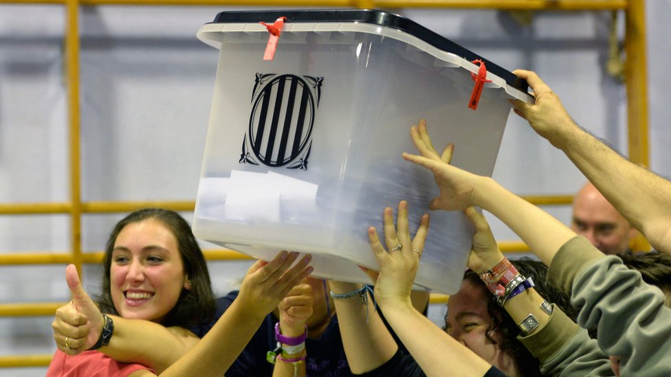 People smiling hold aloft a ballot box, shut and sealed with anti-tamper ties, as they celebrate the end of polling day