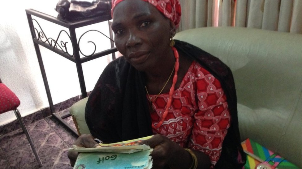 Naomi Adamu's mother Kolo holding one of the notebook diaries