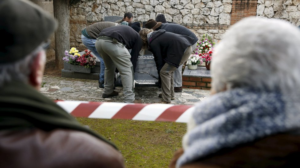 Ascension Mendieta (R) looks on as her father Timoteo's remains are exhumed at Guadalajara cemetery (19 Jan)