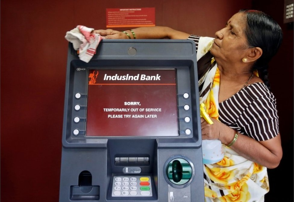 A woman cleans an ATM which is out of service in Mumbai, India, November 11, 2016