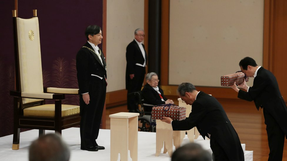 Japan's Emperor Naruhito, flanked by Prince Hitachi, attends a ritual called Kenji-to-Shokei-no-gi