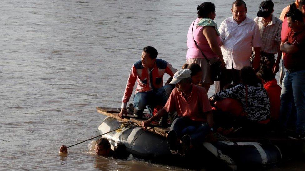 Personas cruzando de Guatemala a México a bordo de una balsa de goma