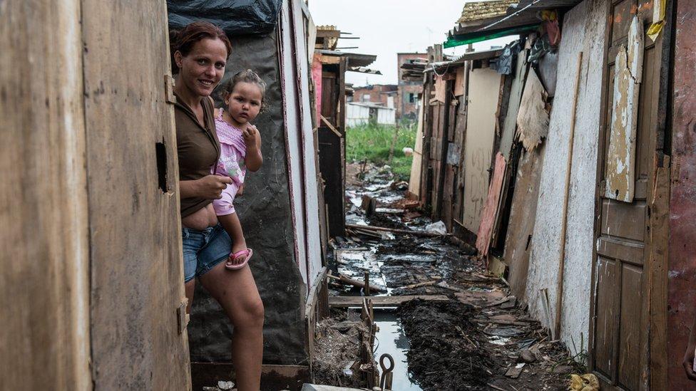 A woman walks inside a favela adjacent to Uniao de Vila Nova