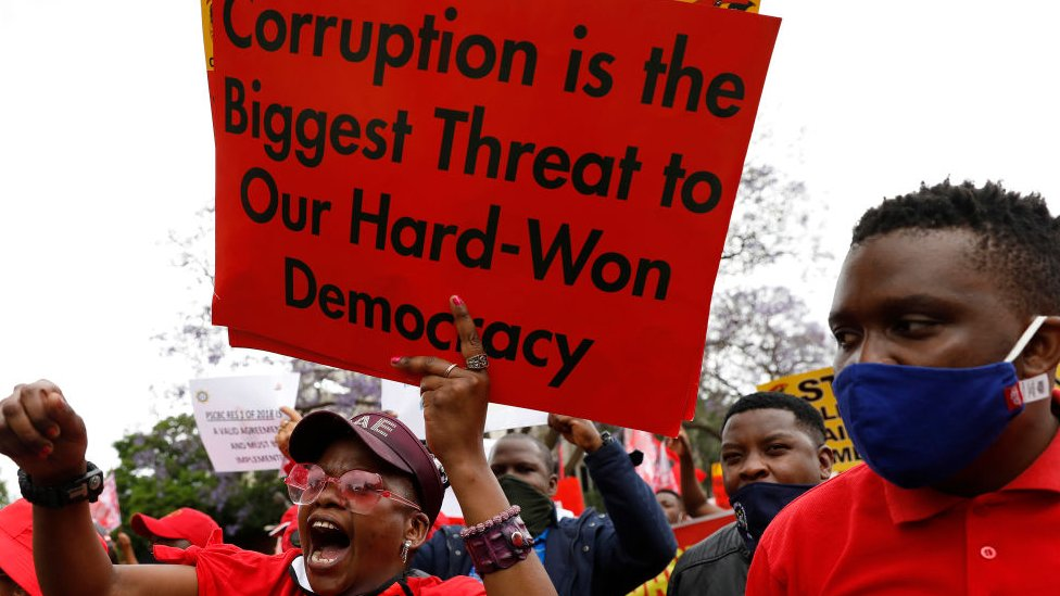 "Someone holds up a sign saying ""Corruption is the greatest threat to our hard-won democracy"" during a trade union strike, Pretoria, South Africa - October 7, 2020"
