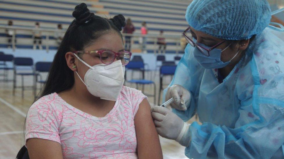 Niña ecuatoriana recibiendo su vacuna de covid-19