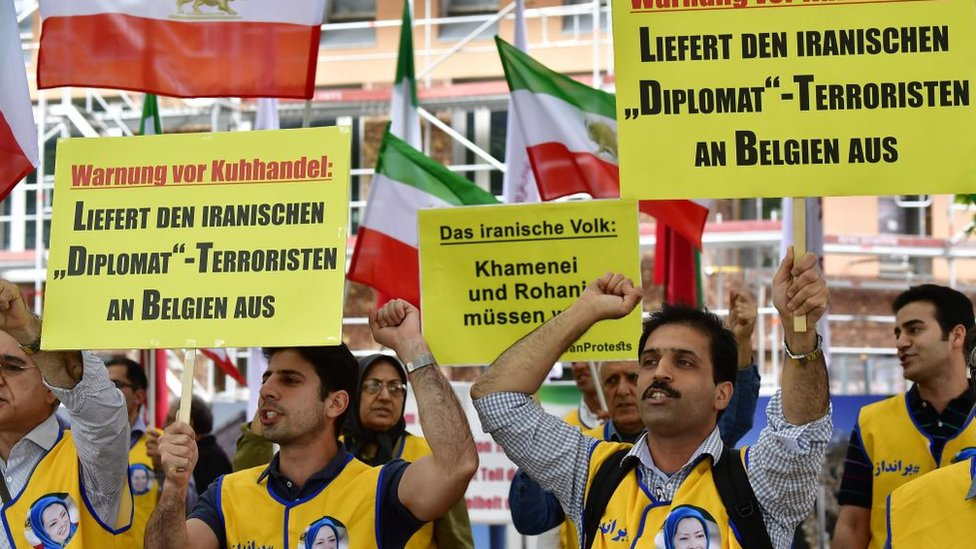 "Supporters of the National Council of Resistance of Iran (NCRI) hold placards reading ""Deliver the Iranian 'diplomat'-terrorist to Belgium"" in Berlin, Germany (11 July 2018)"