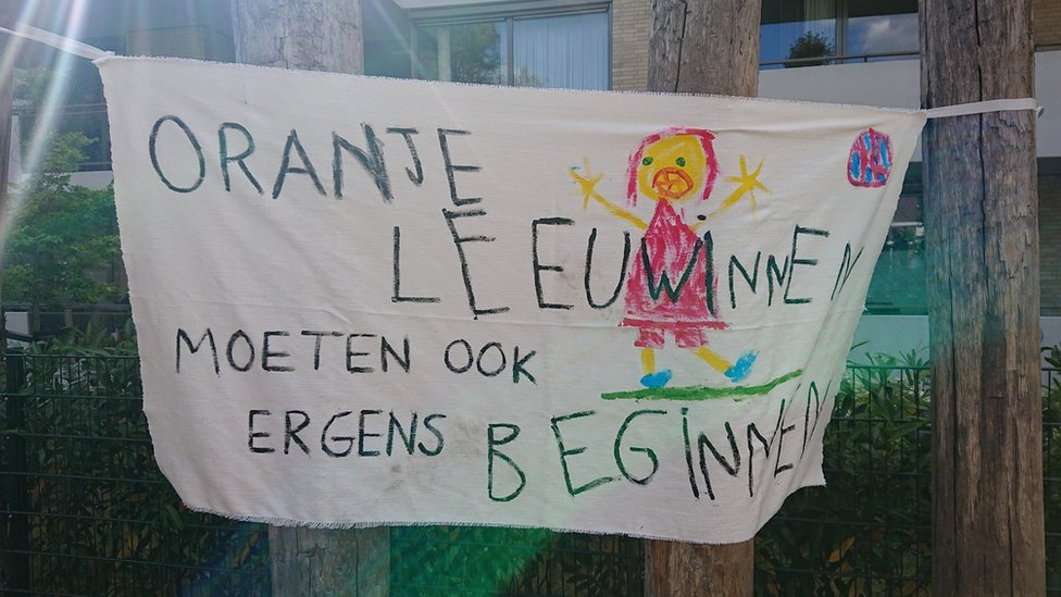 "A banner reads ""Orange Lionesses must also start somewhere"" at the De Buut primary school playground"