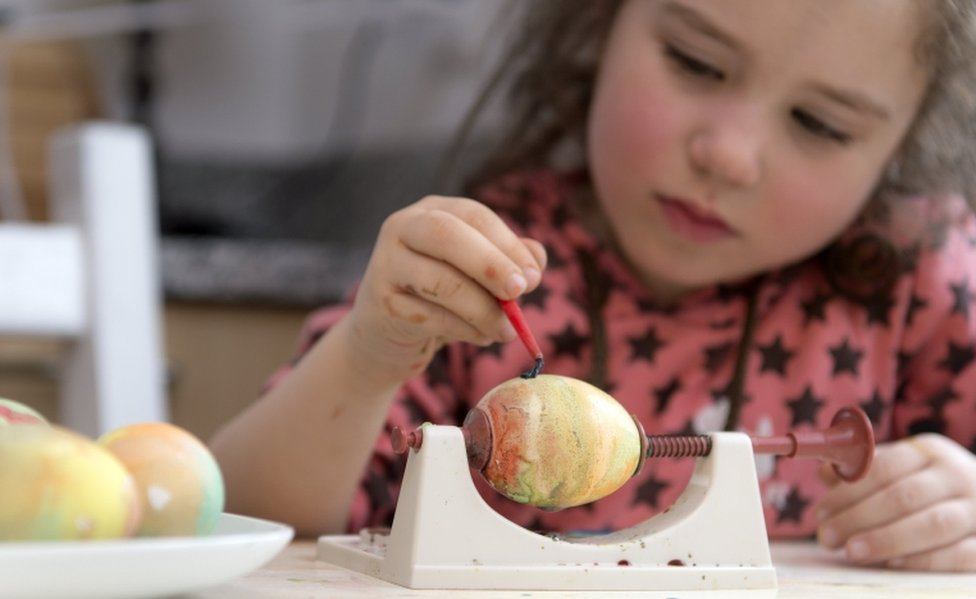 A young girl paints a marbled egg held still in a vice