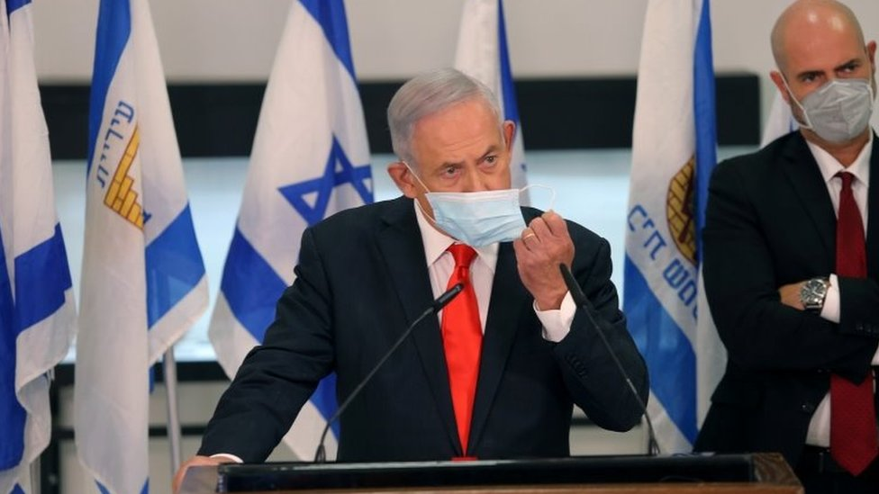 "Israeli Prime Minister Benjamin Netanyahu adjusts his face mask while announcing night-time curfews in 40 ""red"" areas (8 September 2020)"