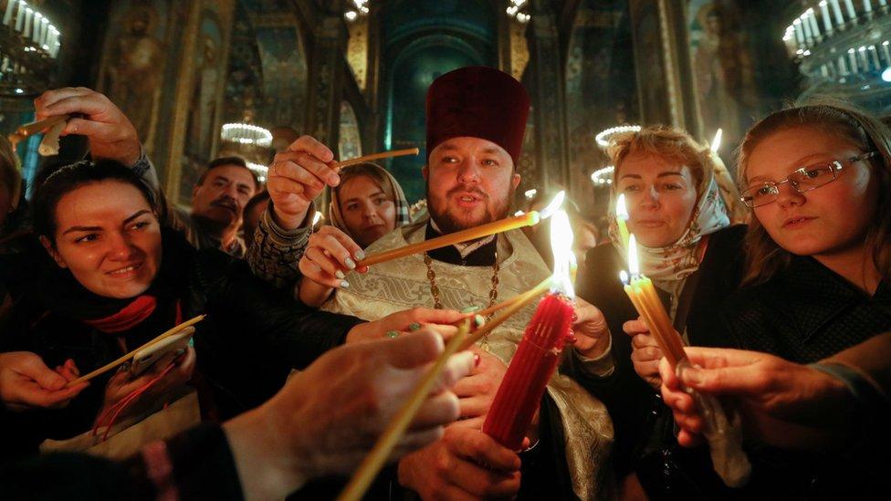 Vernici u Ukrajini pale sveće tokom uskršnje liturgija u Kijevu