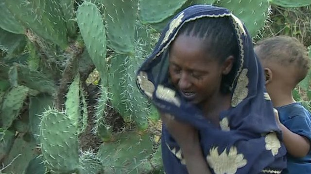 Weeping woman with baby in Ethiopia