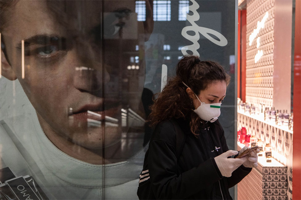A woman checks her mobile phone with a large advertising poster of a face behind her