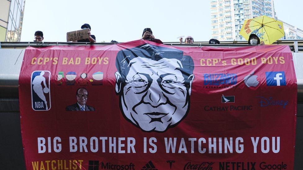 Una pancarta de protesta con una caricatura de Xi Jinping y el eslógan