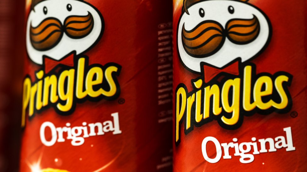 A stock image shows a close-up of two tins of original flavour Pringles crisps.