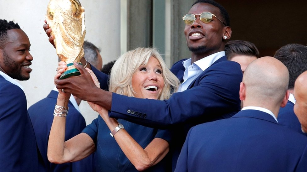 Brigitte Macron and player Paul Pogba hold the World Cup trophy at the Elysée palace in Paris on 16 July 2018