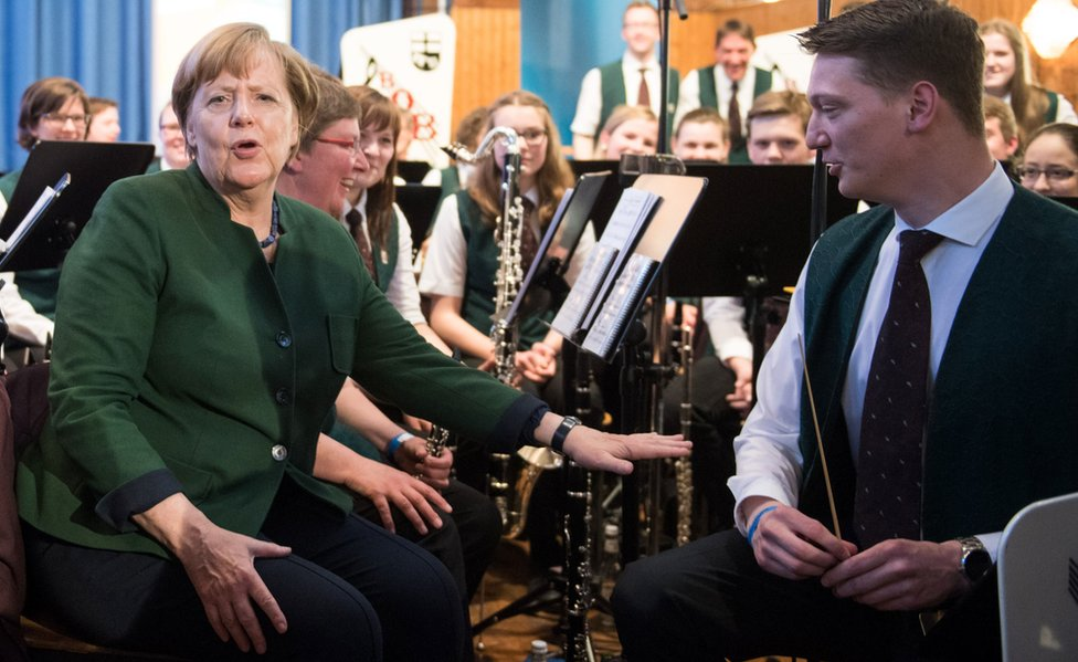 German Chancellor Angela Merkel speaks with musicians of a band at an election rally in Brilon